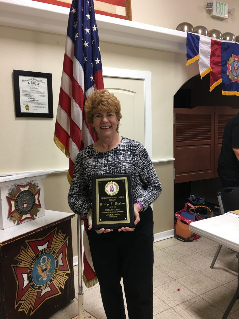Marilyn holding plaque honoring her as an inductee into US Master Weightlifting Hall of Fame